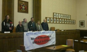 """occupying the mayor's table.  Angry mental health users hung a banner across the top platform of the council chamber """